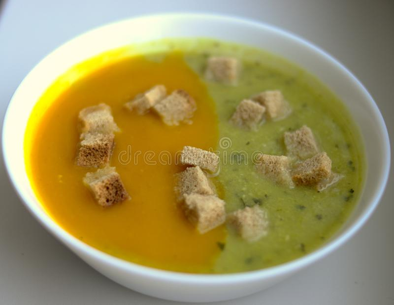 Zucchini and melon soup with croutons in white plate stock image