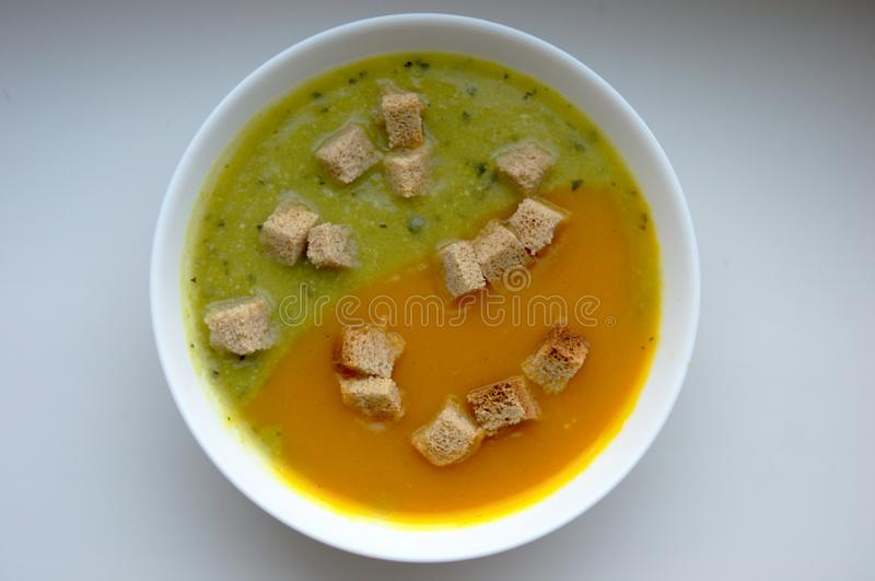Zucchini and melon soup with croutons in white plate royalty free stock images