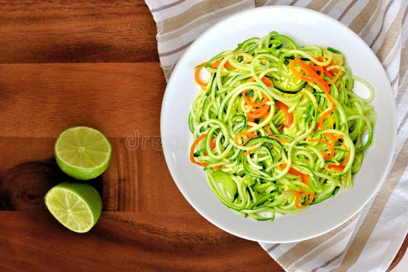 Zucchini noodle dish with lime on wood background. Healthy low carb zucchini noodle dish with carrots and lime on wood background, overhead view royalty free stock photos