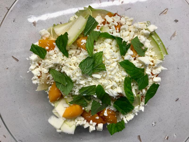 Zucchini- och aprikossallad med ost- och mintkaramellsidor ordnar till f?r att blanda f?r ?ter royaltyfri foto