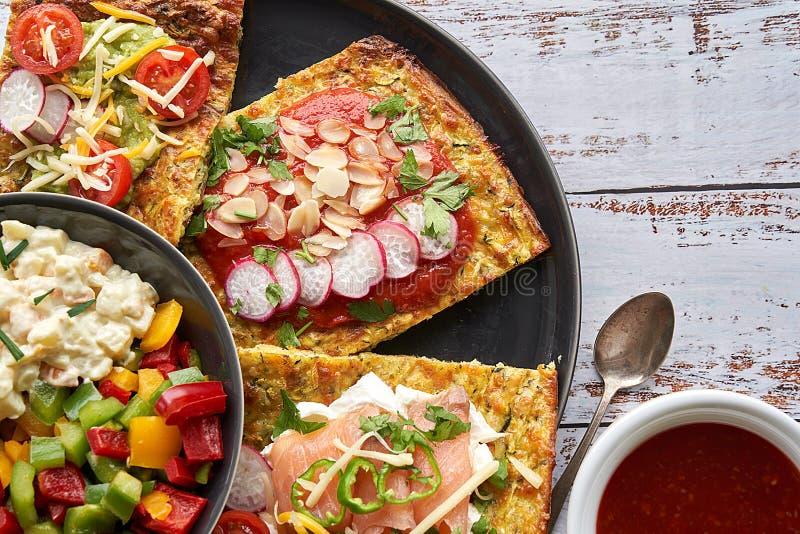 Cheese and zucchini tortillas, smoked salmon, raishes, cherry tomatoes, avocado cream, cream cheese, tomato cream with basil. royalty free stock image