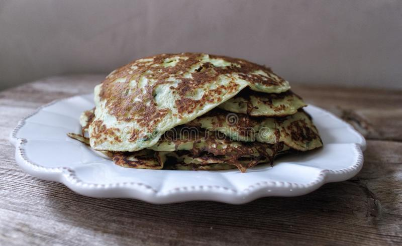 Zucchini pancakes with herbs stack on white plate. Vegetable harvesting concept royalty free stock photo