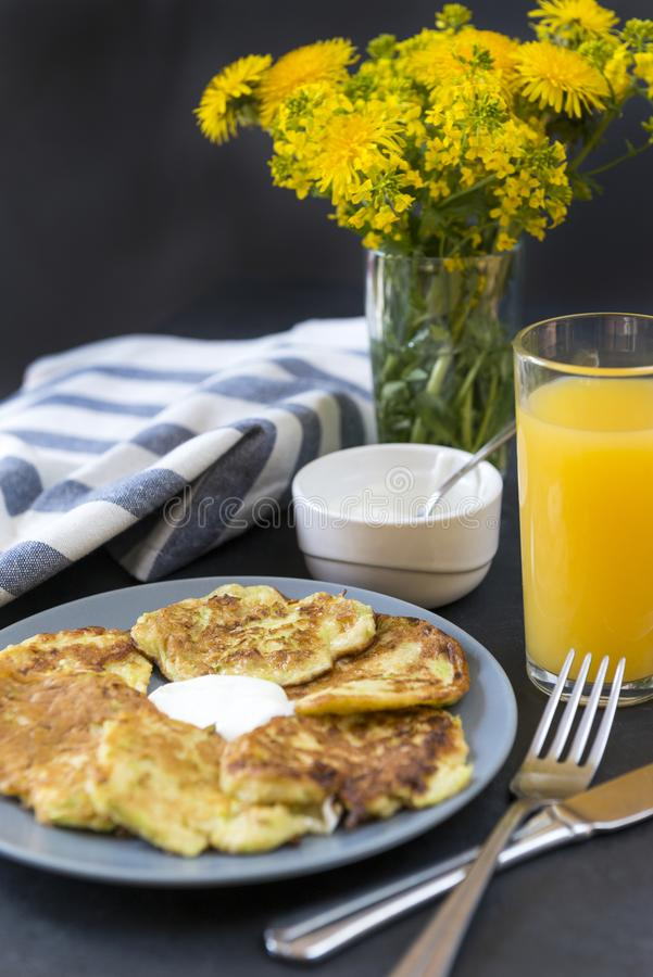 Zucchini pancakes with sour cream on a plate, a glass of orange juice ,a bouquet of yellow flowers, dandelions, towel, fork ,spoon royalty free stock image