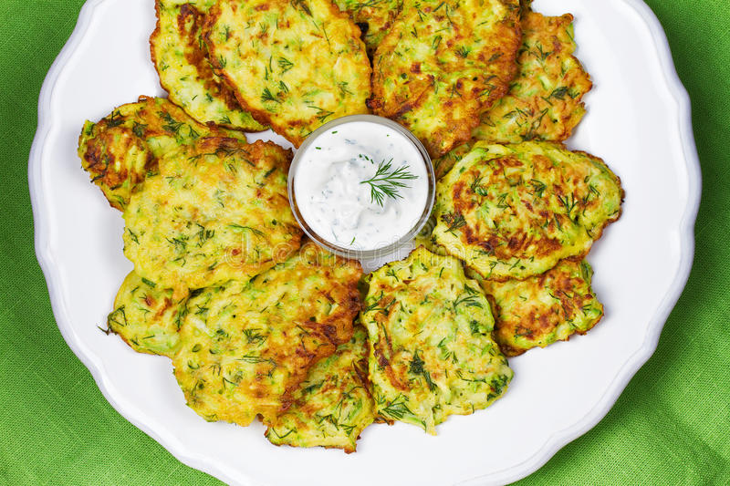 Zucchini Pancakes With Sour Cream. In White Plate. View from above, top studio shot royalty free stock image