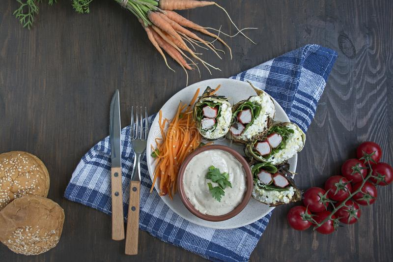 Zucchini roll with crab sticks, eggs and spinach. Delicious appetizer served on a round plate with sauce and fresh vegetables and. Herbs. View from above.Proper stock image