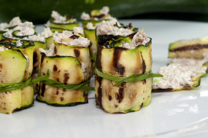 Zucchini rolls with cheese. Grilled zucchini rolled with cream cheese in a white plate stock images