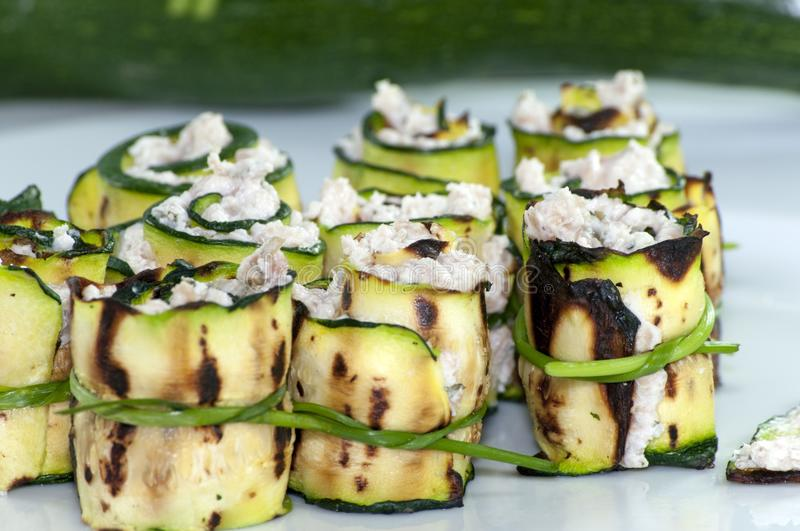 Zucchini rolls with cheese. Grilled zucchini rolled with cream cheese in a white plate royalty free stock images
