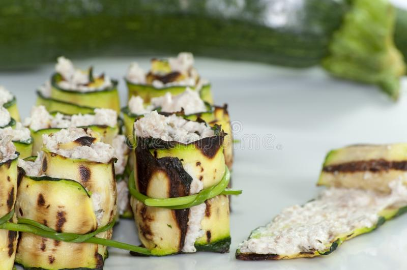Zucchini rolls with cheese. Grilled zucchini rolled with cream cheese in a white plate stock photos