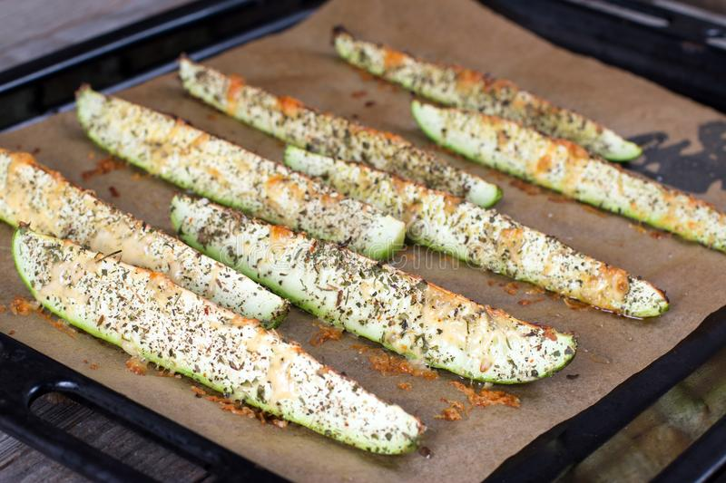 Zucchini slices with grated cheese on baking paper brown baking paper ready to bake. Close up of zucchini slices with grated cheese over brown baking paper ready royalty free stock photos