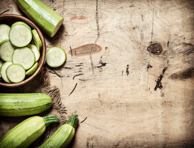 Zucchini som skivas och som är hel av det gamla tyget royaltyfria bilder