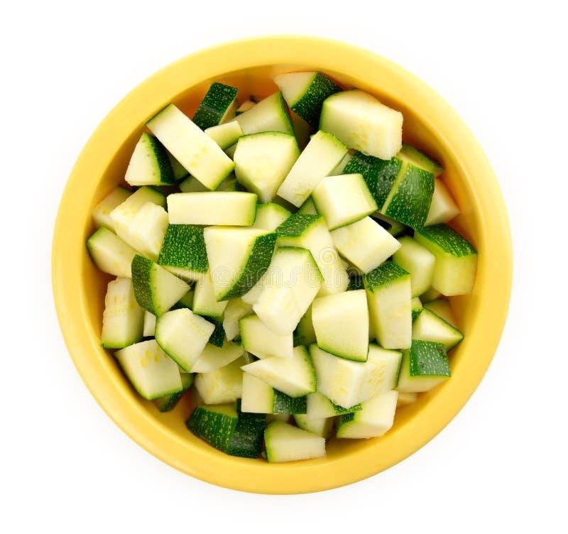 Zucchini tagliato in una ciotola isolata su bianco immagine stock