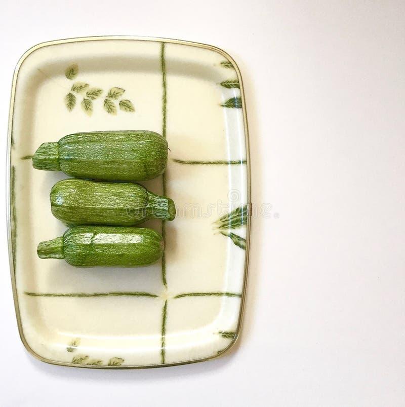 Zucchini tre på vit magasin för ett gräsplan och fotografering för bildbyråer