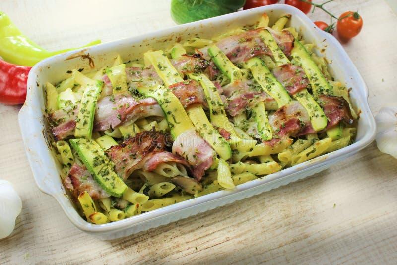 Zucchini und Speck backten Teigwaren mit Käse und Parmesankäse im weißen Topf auf dem bunten Gemüse des weißen Holztischs stockbilder