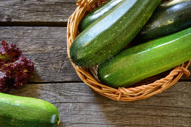 Zucchini in wicker basket with vegetables around. Harvest. View from above. stock photography