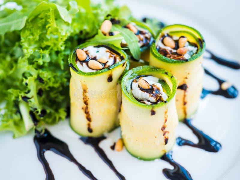 Zucchinin rullar med mascarponeost, muttrar, grön sallad och soya arkivfoton