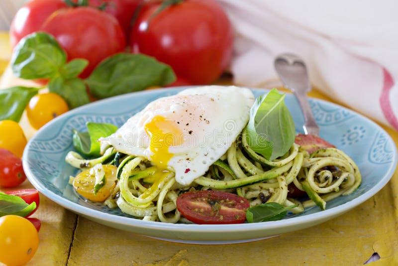 Zucchininudlar med tomater och ägget arkivfoton