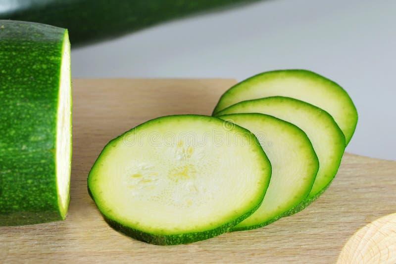 Zucchiniskivor på träbräde royaltyfria foton