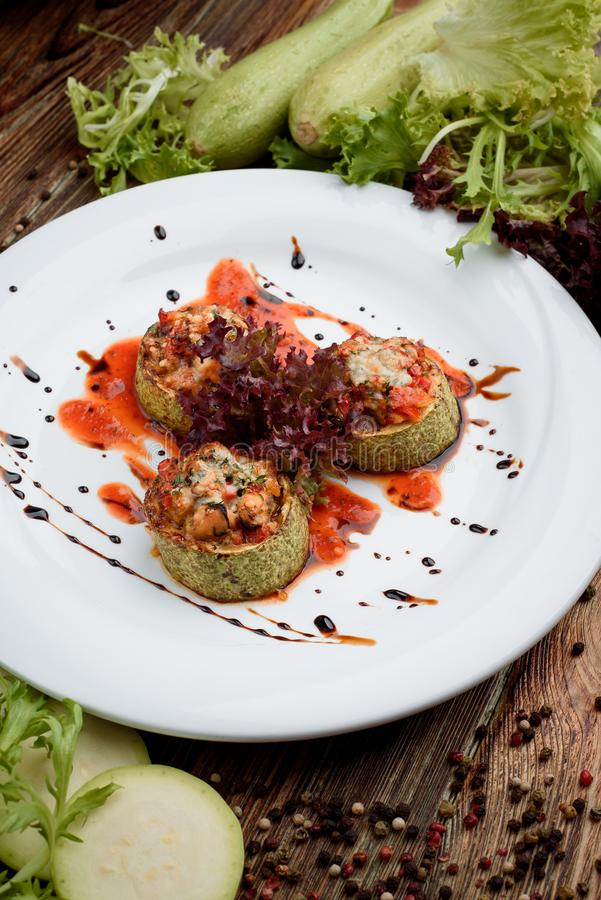 Zucchiniskivor som stoppas med grönsaker i tomatsås på den vita plattan med grönsallat på mörk träbakgrund fotografering för bildbyråer