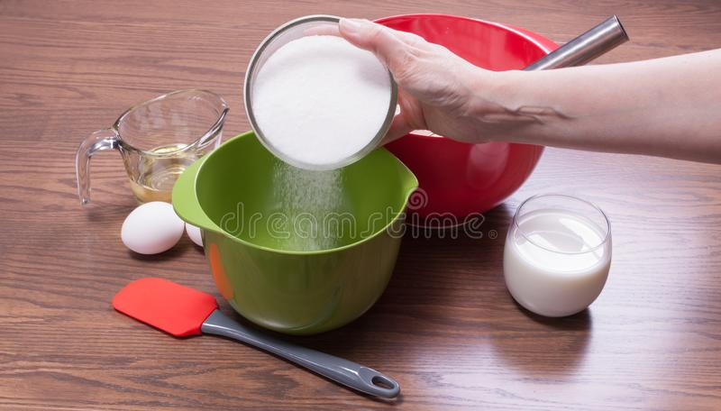 Zucker in einer Schüssel gießen, um Kuchen zu machen lizenzfreie stockfotos