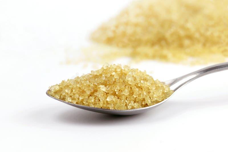 Zucker im Löffel, zuckert braunen Haufen vom Zuckerrohr auf Gelb des Löffeledelstahls und des granulierten Zuckers des Hintergrun lizenzfreie stockfotos
