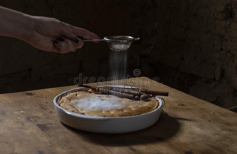 Zuckerglasurapfelkuchen der Frau Hand lizenzfreie stockfotos