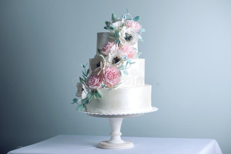 Zuckern die abgestufte weiße Hochzeitstorte schöne drei, die mit Blumen verziert wird, rosa Pfingstrosen Konzept von eleganten Fe lizenzfreie stockbilder