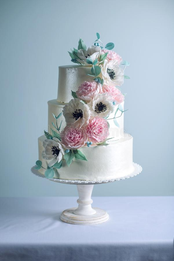 Zuckern die abgestufte weiße Hochzeitstorte schöne drei, die mit Blumen verziert wird, rosa Pfingstrosen Konzept von eleganten Fe lizenzfreies stockbild