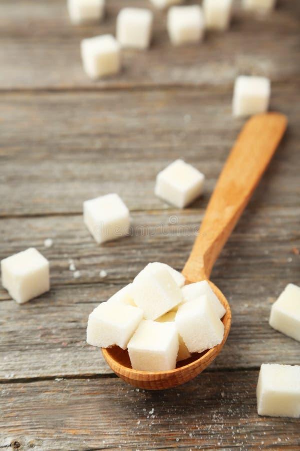 Zuckern Sie Würfel im Löffel auf grauem hölzernem Hintergrund stockbild