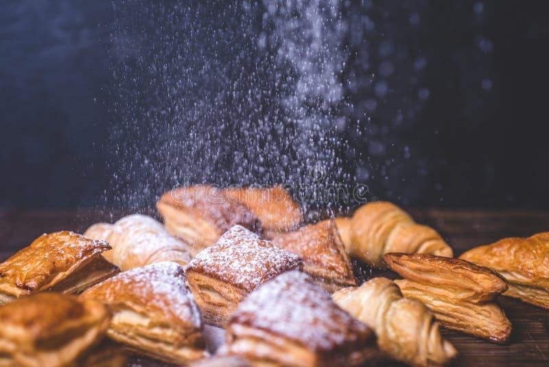 Zuckerpulver wird auf Brötchen vom Blätterteig geschüttet stockbilder
