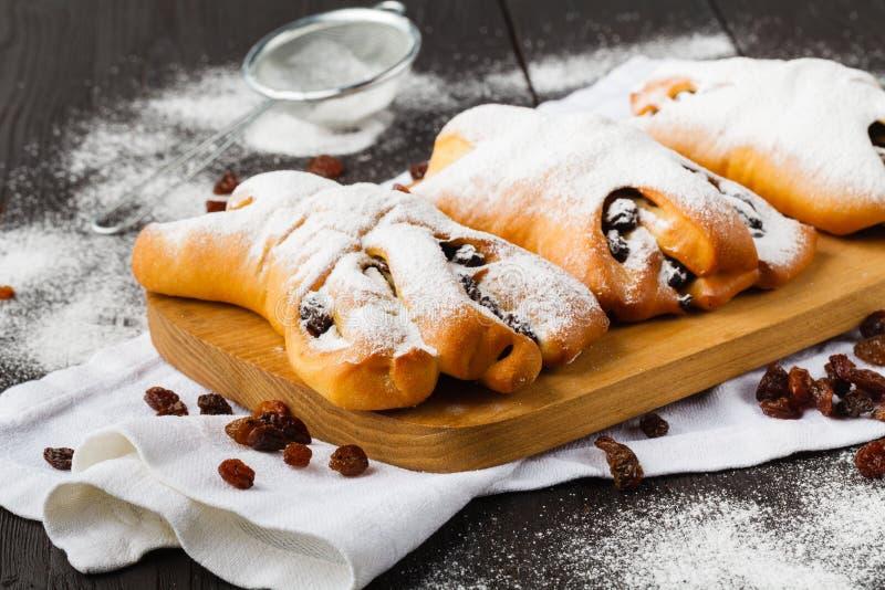 Zuckerpulver wird auf ein frisch gebackenes croissan gesch?ttet stockbilder