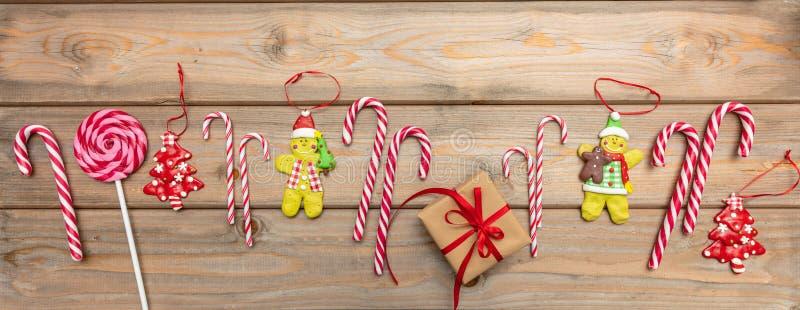 Zuckerstangen, Weihnachtsverzierungen und eine Geschenkbox mit rotem Band auf hölzernem Hintergrund, Fahne, Draufsicht lizenzfreie stockfotografie
