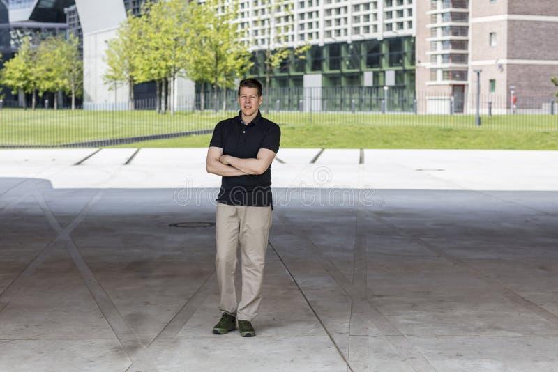 Zufällig gekleideter Mann, der vor Bürogebäuden steht lizenzfreie stockbilder