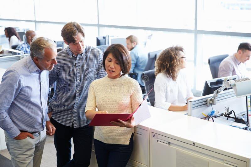 Zufällig gekleidetes Personal, das in einem beschäftigten Bürogroßraum steht lizenzfreie stockfotos