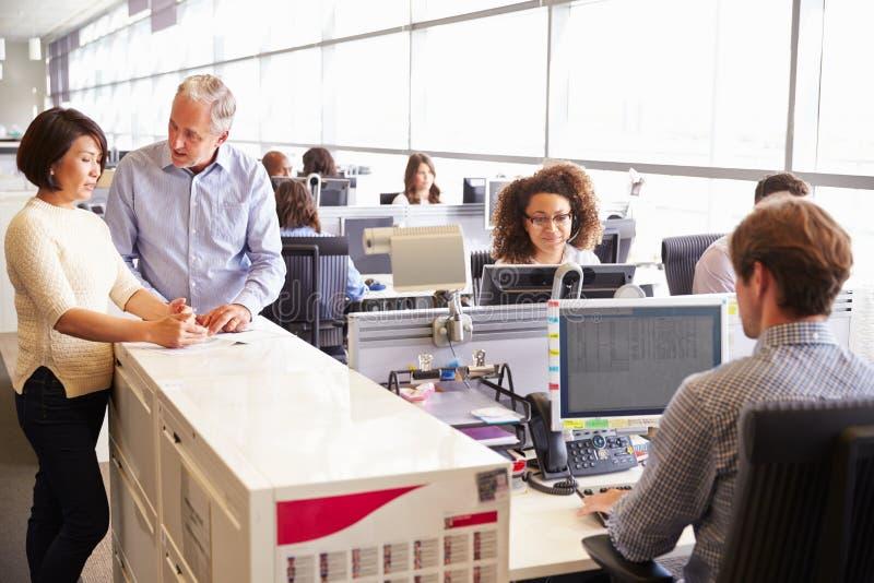 Zufällig gekleidetes Personal, das in einem beschäftigten Bürogroßraum steht stockfoto