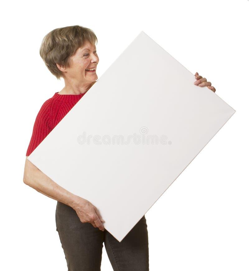 Zufällige ältere Dame, die Zeichen hält. lizenzfreies stockbild