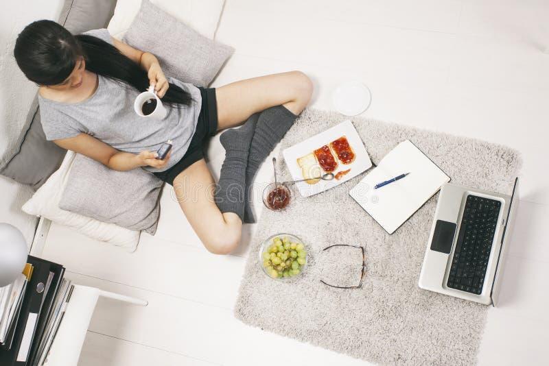 Zufällige asiatische Frau, die frühstückt und im Haus arbeitet. lizenzfreie stockbilder