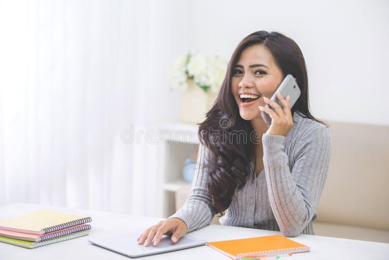 Zufällige asiatische Frau, die zu Hause einen Telefonanruf unter Verwendung des intelligenten Telefons macht stockfoto