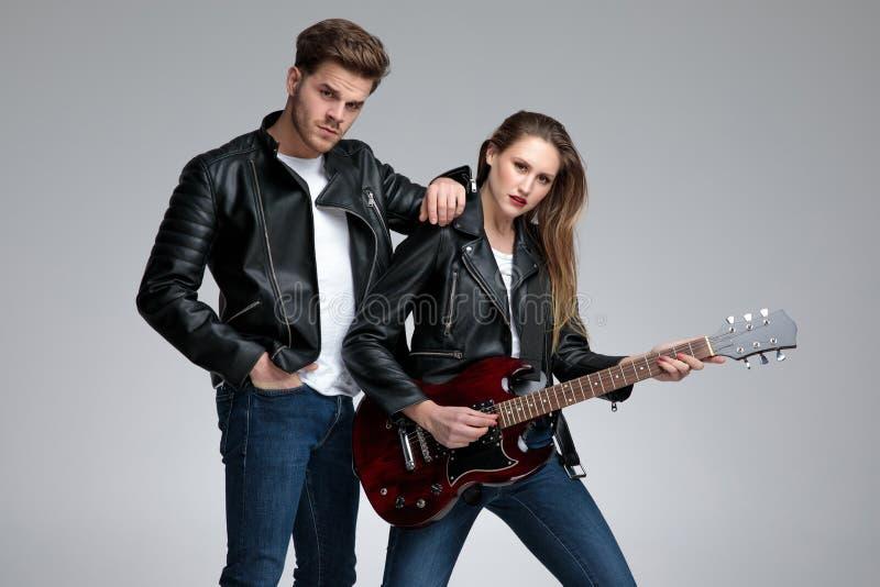 Zufällige aufwerfende Paare, während sie E-Gitarre spielt stockfotos