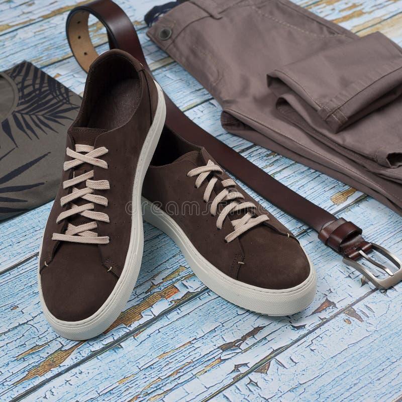 Zufällige Ausstattung der Männer Die Schuhe der Männer, Kleidung und Zusätze auf hölzernem Hintergrund - Jeans, Hemd, Turnschuhe, stockfotografie