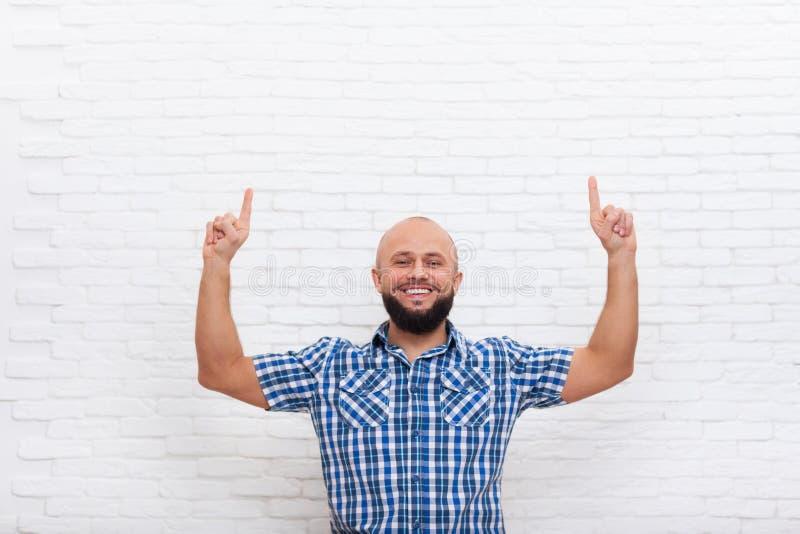 Zufällige bärtige Geschäftsmann-lächelnde Punkt-Finger oben lizenzfreie stockfotografie