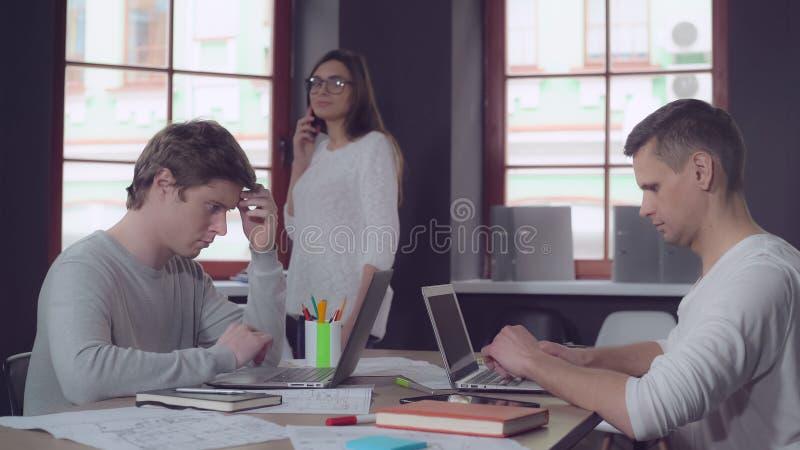 Zufällige fokussierte Leute, die mit Computer arbeiten lizenzfreies stockbild