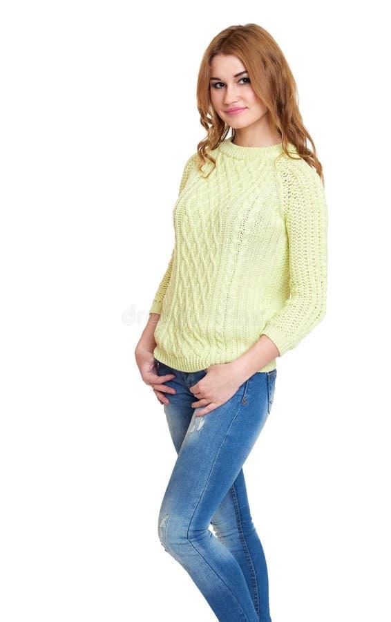 Zufällige gekleidete Jeans des jungen Mädchens und grüne eine Strickjacke, die im Studio auf weißem Hintergrund aufwirft lizenzfreies stockfoto