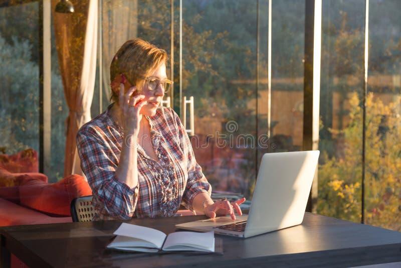 Zufällige Geschäfts-Person, die an dem Computer spricht am Telefon arbeitet stockbild