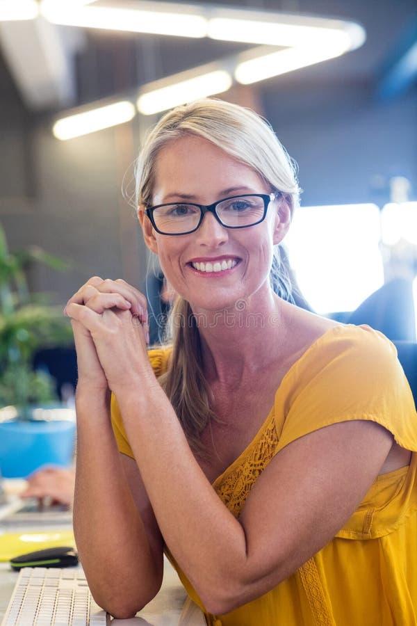 Zufällige Geschäftsfrau, die an der Kamera lächelt lizenzfreie stockbilder