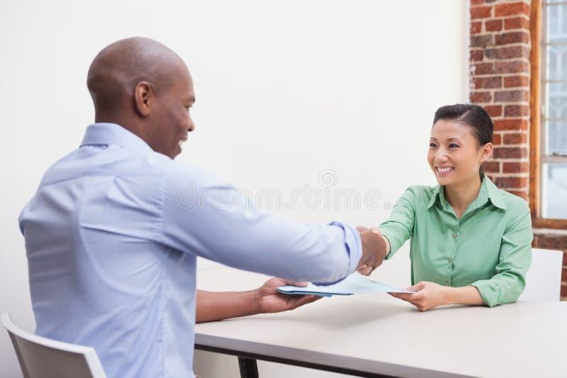 Zufällige Geschäftsleute, die Hände am Schreibtisch rütteln stockfoto