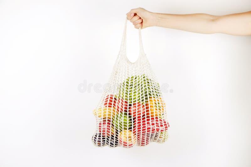 Zufällige junge Frau übergibt das Halten des Bündels verschiedener Obst und Gemüse im recyclebaren Schnursack lizenzfreie stockbilder