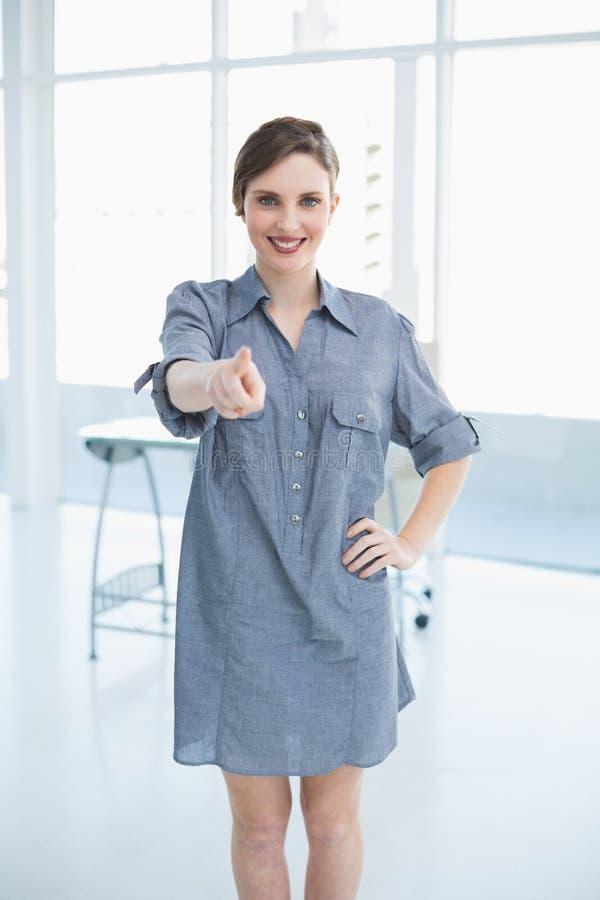 Zufällige junge Geschäftsfrau, die im Büro aufwirft lizenzfreie stockbilder