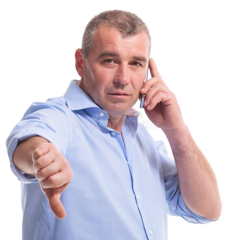 Zufällige Mitte alterte Manndaumen unten am Telefon stockfotos