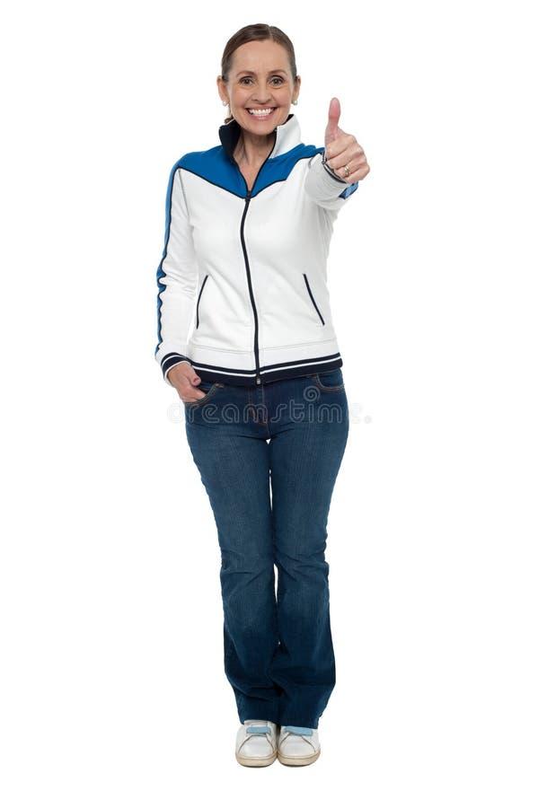 Zufällige reizend Frau, die oben Daumen gestikuliert stockfoto