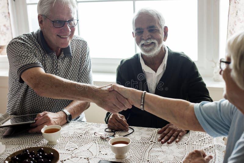 Zufällige Senioren, die zusammen Hände rütteln stockbilder